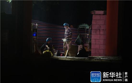 6月16日凌晨,法医等工作人员在江苏省丰县创新幼儿园门前做清理、鉴定工作。新华社记者李响摄