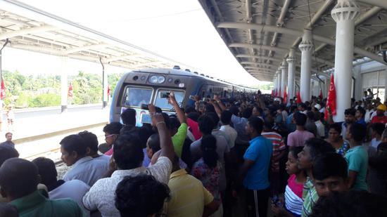 在斯里兰卡南部城市贝利亚塔,人们拍照驶入车站的火车。(新华社)